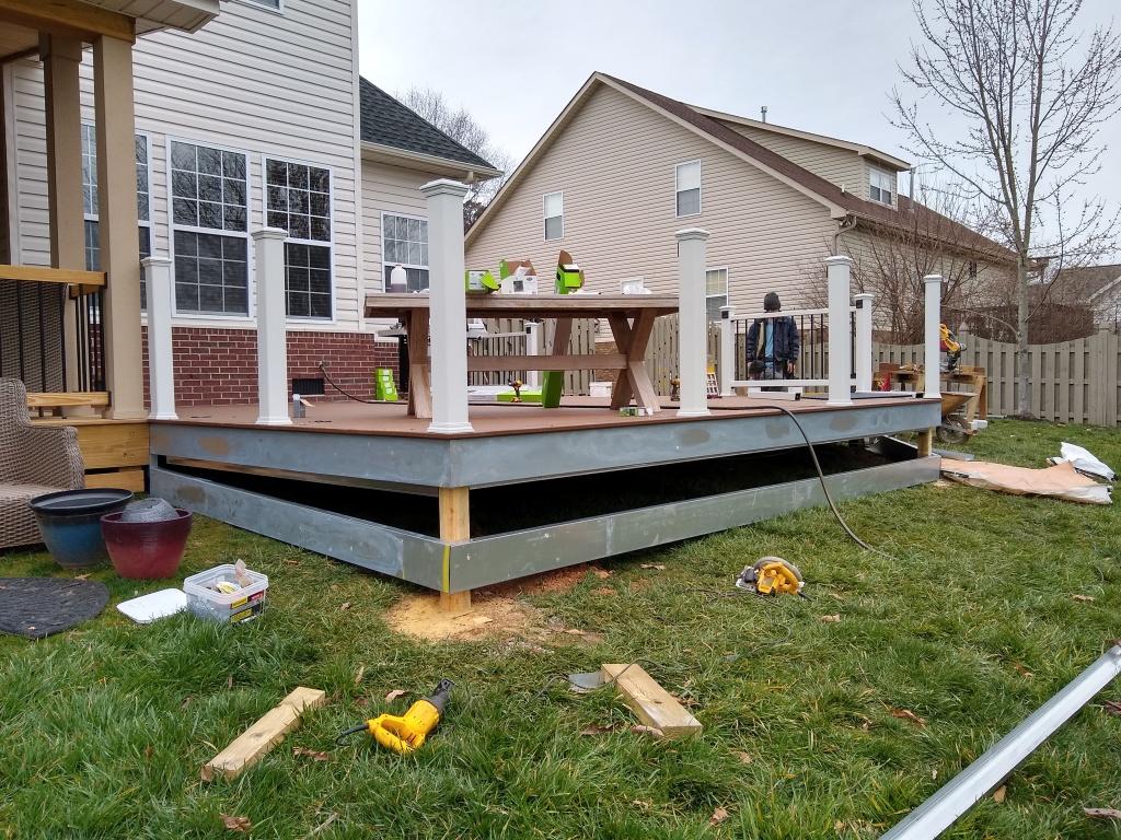 Deck builders installing handrail post